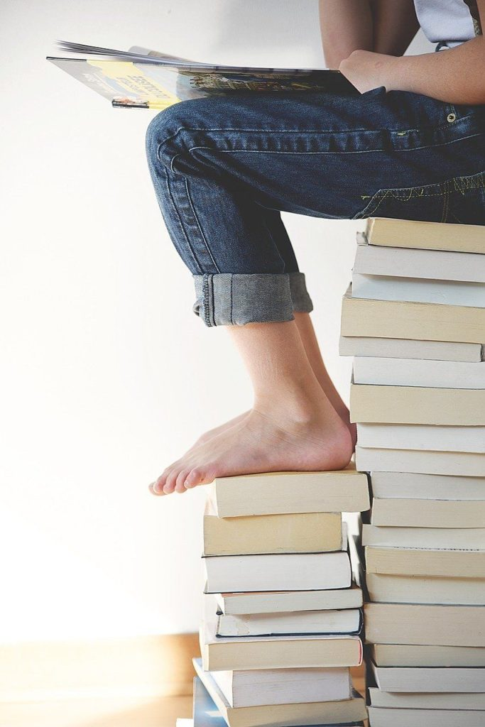 大量の本の上に座る女性