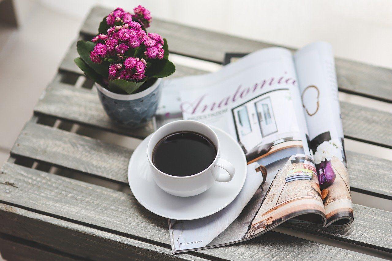 机に置かれた英字新聞とコーヒー