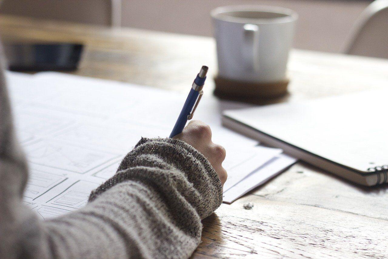 ノートに何かを書く女性