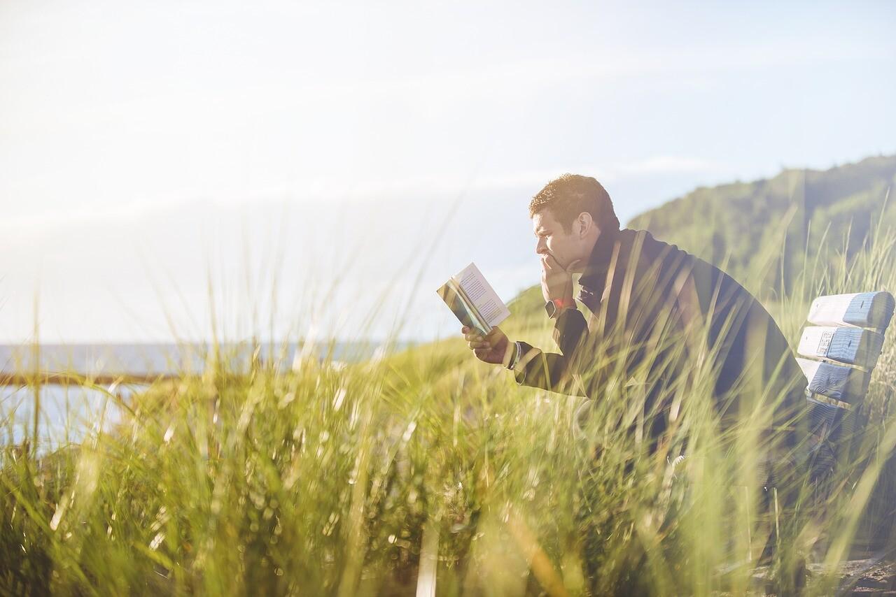 河原で本を読む男性