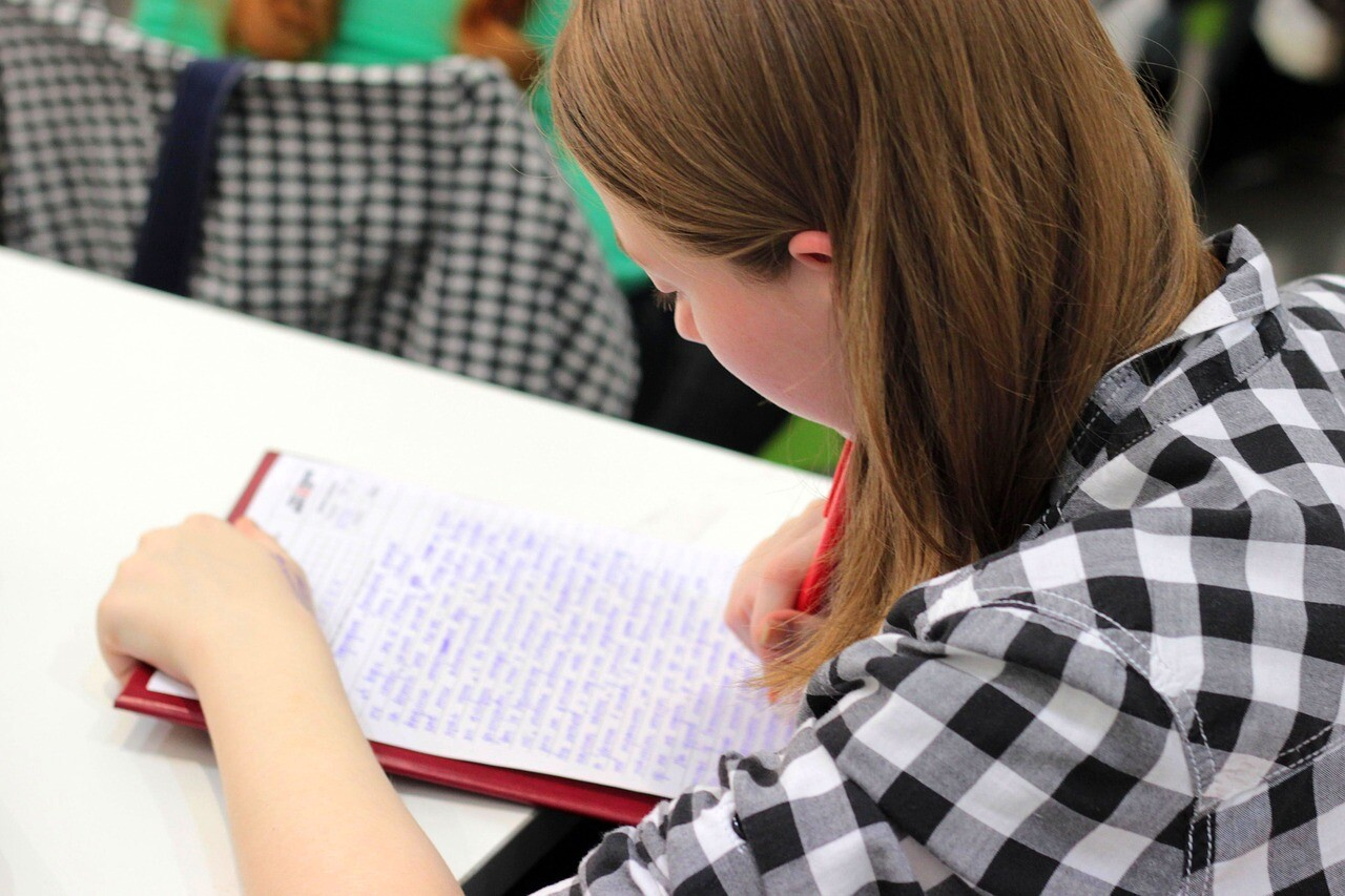 ノートに英語を書き写す学生