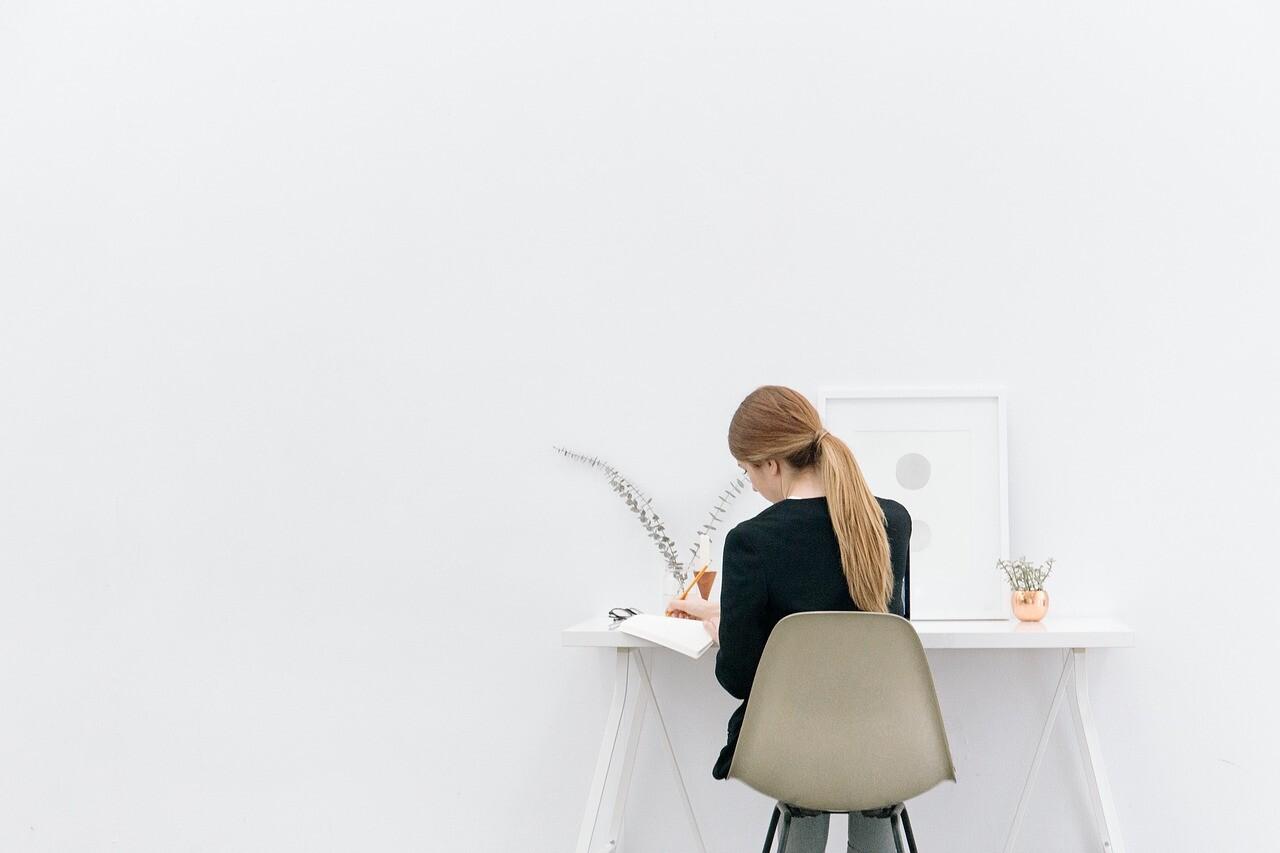 机に座り問題を解く女性