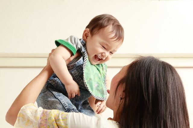 赤ん坊を持ち上げる母親